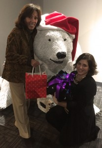 Joy and Kelly pose with a friendly polar bear and their sock donations.
